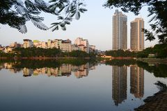 City lake and public park in Hanoi, Vietnam. Public city park near Tay lake in the downtown district of Hanoi, Vietnam. Residential houses reflected in water Stock Photo