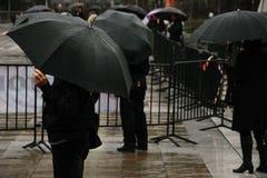 Public dans l'attente de noir/observation d'un événement de ville sous la pluie photos stock