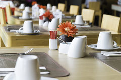 Public dining table set. Public wood dining table set with white porcelain tableware and decorative objects Stock Image