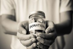 Public donation charity event concept. Money coin in bottle glasse Royalty Free Stock Image