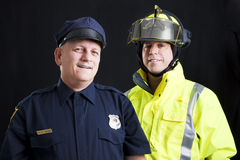 Public Employees Happy. Public employees, a firefighter and a police officer, smiling and happy.  Black background Royalty Free Stock Photos
