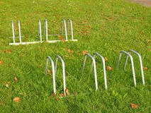 Public empty stand for bikes on grass. Gray iron frame with marks of corrosion. Royalty Free Stock Images