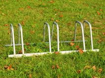 Public empty stand for bikes on grass. Gray iron frame with marks of corrosion. Stock Images