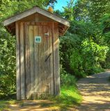 Public facility. A wooden public washroom along a path in a nature park in Montreal Canada Royalty Free Stock Photo