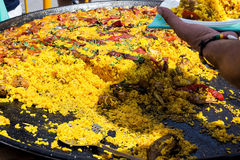 Public fest in Spain. Large flat frying pan with colorful cooked paella. Selling to guests. Outdoors, picnic Stock Image