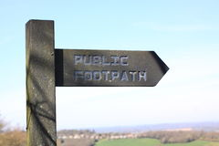 Public footpath sign. Wooden signpost marking a public right of way footpath over fields and countryside in England Stock Photo