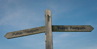 Public Footpath Sign in England. Set against a blue sky with wispy cloud Royalty Free Stock Images