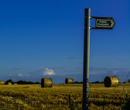 Public Footpath Sign. With straw bales,stubble and blue  sky Stock Photos