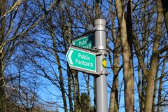 Public footpath sign in the UK against blue sky and trees. A green public footpath directional sign against blue sky and trees royalty free stock photos