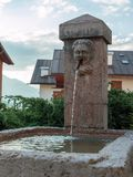 Public Fountain in Mountain`s Village among Houses Royalty Free Stock Images
