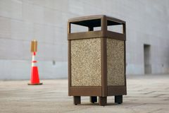 Public Garbage Can. An open public space with brown garbage can in focus Stock Image