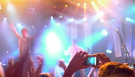 Public having a good time during a concert. With the stage full of lights Royalty Free Stock Photography