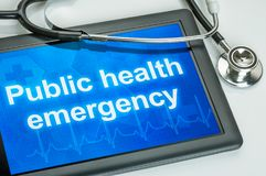 Public health emergency writtrn on the display. Tablet with the text Public health emergency on the display Stock Photo