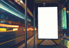 Public information board with blurred vehicles in high speed in night city. Illuminated blank billboard with copy space for your text message or content Royalty Free Stock Image