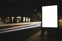 Public information board in night city with shutter speed on background, empty advertising mock up banner on roadway Stock Images