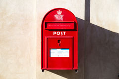 Public letterbox in Denmark. Copenhagen, Denmark - November 03, 2016: A traditional red public letterbox hanging on a wall Royalty Free Stock Images