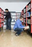 Public Library. Two men, looking throught the books in bookselves at a public library Stock Image