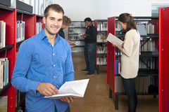 Public Library. Man, smiling into the camera, whilst browing through a book, surrounded by bookshelves in a public library with several other customers in the royalty free stock photo