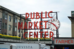 Public market center sign and clock, Seattle, Wash. The public market center sign with Clock stands bowled against the spring background sky. March 2013 Royalty Free Stock Photo