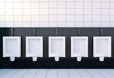 Public men's toilet room interior with white urinals row on white tiles wall and floor Royalty Free Stock Photography