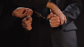 Public official handcuffed, charged with bribery, political corruption, closeup. Stock footage stock footage