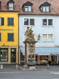 Public old drinking water tap with statue on the street in Wurzb Stock Image