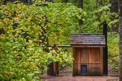 McKenzie Pass public outhouse and fall colors. A public outhouse sits along side the McKenzie Pass scenic highway amongst autumn turning leaves on trees and royalty free stock photos