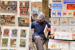 Public painter with his paintings in Place du Tertre square in Paris Royalty Free Stock Photo