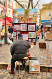 Public painter with his paintings in Place du Tertre square in Paris' XVIIIe arrondissement (Montmartre) Royalty Free Stock Photography