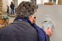 Public painter with his paintings in Place du Tertre square in Paris' XVIIIe arrondissement (Montmartre) Royalty Free Stock Photos