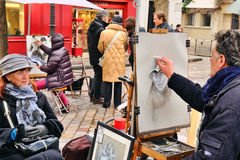 Public painter with his paintings in Place du Tertre square in Paris' XVIIIe arrondissement (Montmartre) Royalty Free Stock Photos
