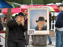 Public painter on Montmartre screening his face Royalty Free Stock Image
