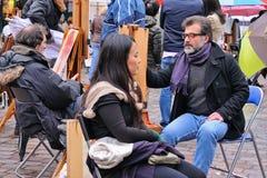 A public painter paints for a tourist in Place du Tertre square in Paris' XVIIIe arrondissement (Montmartre) Royalty Free Stock Images