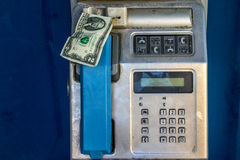 A public payphone with two dollar banknote looking out Royalty Free Stock Photos