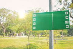 Public park with empty green trailhead sign showing multiple trails and nature landscape background in morning. Green sign in park with flare light royalty free stock photo