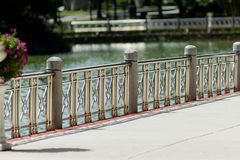 Public park Polished metal banister railings barrier to lake edg. E on sunny day Royalty Free Stock Image