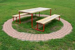 Public park table connected to two benches made of dilapidated wood and metal surrounded with decorative stone tiles and uncut. Grass on warm sunny spring day royalty free stock images
