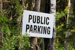 A public parking sign nailed to some trees Stock Photo
