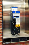 Public payphone. In stainless steel phone booth on red brick wall Royalty Free Stock Photos
