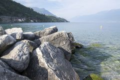 Public pebble beach on the shore of the lake Lago Di Garda, Toscolano Maderno, Italy. Sunny day Royalty Free Stock Image