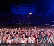 Public. People watching Robbie Williams in concert in Bucharest, Romania. The People's House is in the background Stock Image
