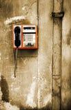 Public phone. Orange phone on monochrome grunge background Royalty Free Stock Photo
