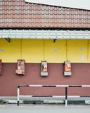 Public phones in dispair. Public phones attached on yellow colored wall. Who uses public phone these days Stock Image