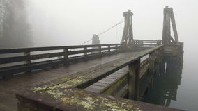 Public Pier, Fraser River Fog. Fog, off the Fraser River, wraps around a pier in the early morning. British Columbia, Canada stock footage
