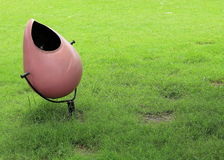 Public dustbin pink recycling container for paper with green bush background royalty free stock photos