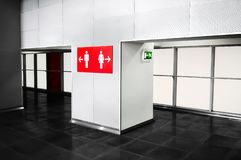 Public place bathroom services indication sign. Toilette navigat. Ion in big modern mall or business center. Grey tones interior design with bright red Stock Photography