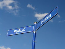 Public and private signpost. Two-way metal blue signpost with public and private indications over blue sky Royalty Free Stock Images