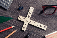 Public Relation crossword on office table collected of wooden cu Stock Photos