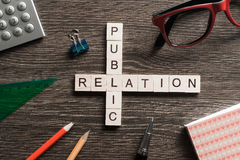 Public Relation crossword on office table collected of wooden cubes Stock Image