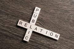 Public Relation crossword on office table collected of wooden cubes Stock Photo